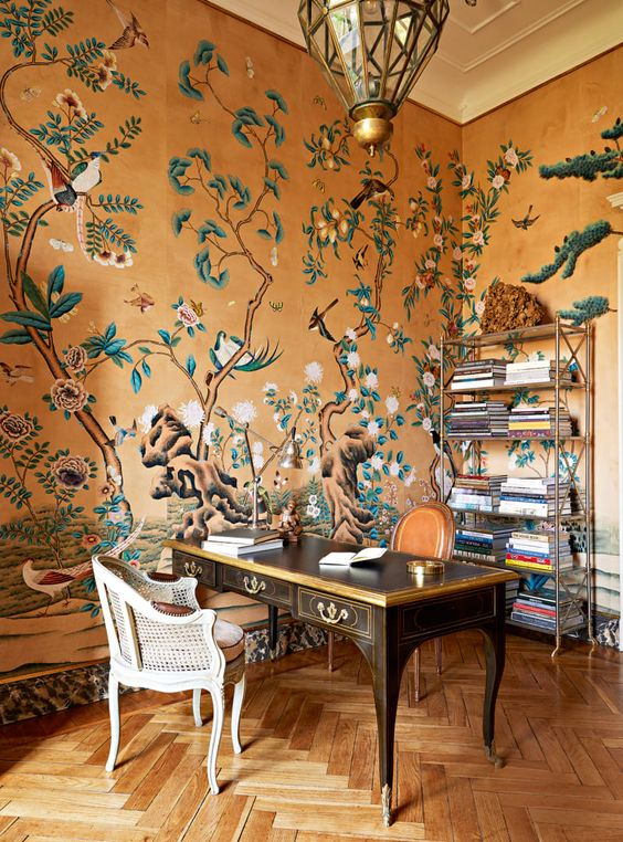 a refined maximalist home office with beautiful wallpaper walls, a refined vintage desk, a rattan chair, a chic faceted pendant lamp and an open storage unit