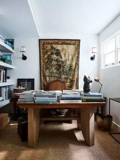 a refined maximalist home office with white walls, floating shelves, a rough wooden desk, a jute rug, baskets and tables and a tapestry