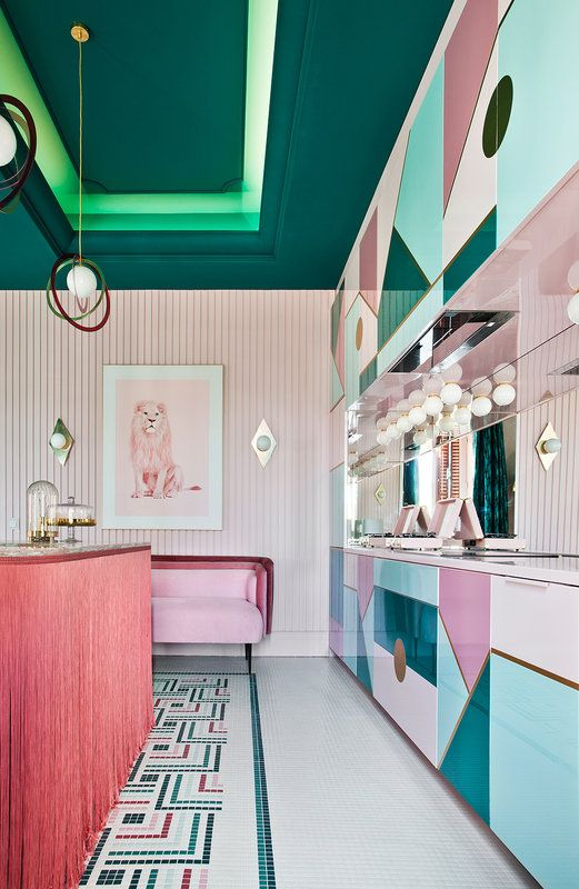 a refined maximalist kitchen with geometric pink, blush and blue cabinets, a pink kitchen island, a pink sofa and a dark green ceiling