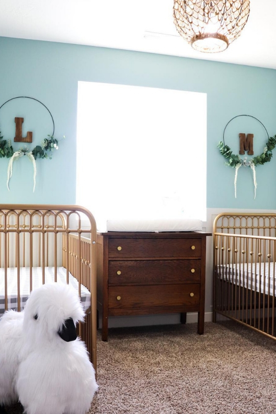a retro-inspired twin nursery with blue walls, metal cribs, a stained dresser, a rug and some pretty wreaths on the wall