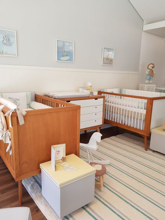 a retro-inspired twin nursery with stained cribs, a stylish dresser, some pretty kids' furniture and a lovely gallery wall