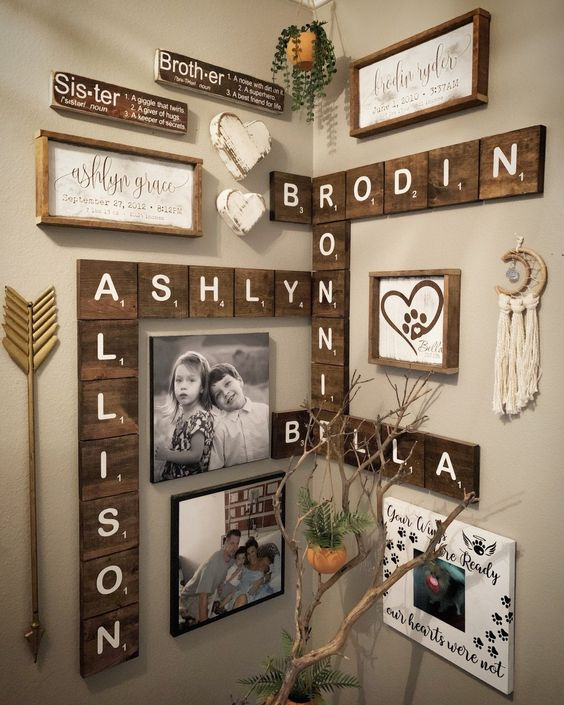 a rustic and boho gallery wall with wooden letters, signs in frames, some branches, arrows, tassels and potted greenery