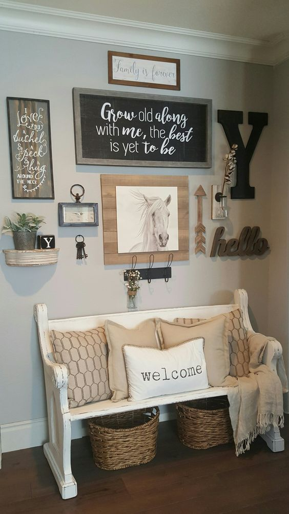 a rustic gallery wall with a chalkboard sign in a frame, artworks, monograms, arrows, a clock and various potted plants