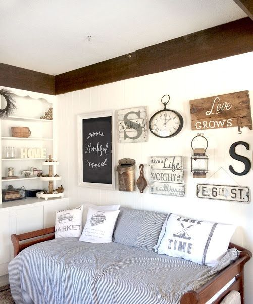 a rustic gallery wall with some signs, a chalkboard sign in a frame, a clock, lamps and some monograms feels vintage