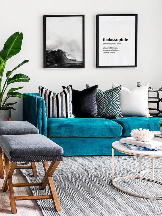 a seaside living room with a turquoise sofa, printed pillows, a black and white gallery wall, grey stools and a round table