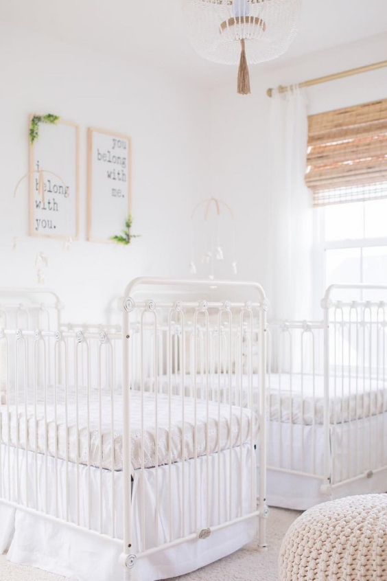 a serene white nursery with vintage white cribs, a knit ottoman, shades, artworks and a pretty chandelier plus matching mobiles