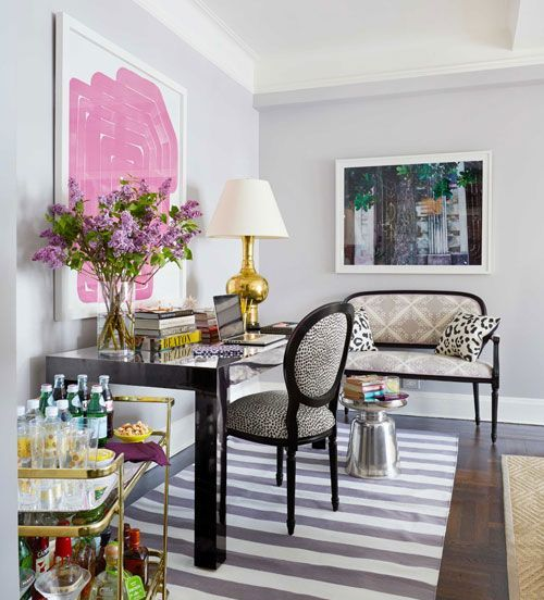 a sophisticated home office with a black desk and animal printed textiles, a striped rug, bold artworks and a gold bar cart is chic