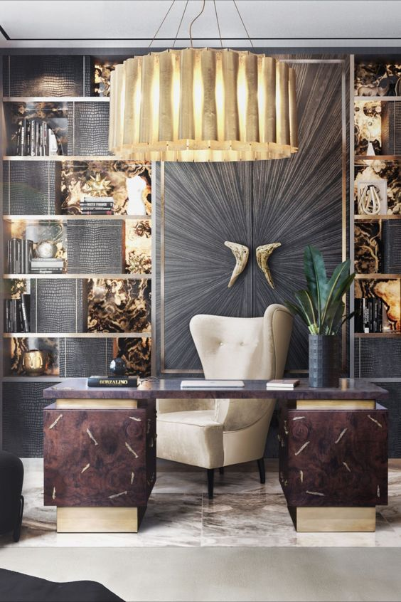 a sophisticated home office with a gold and black wall, shelves, a dark desk and a large wingback chair, a gold pendant lamp