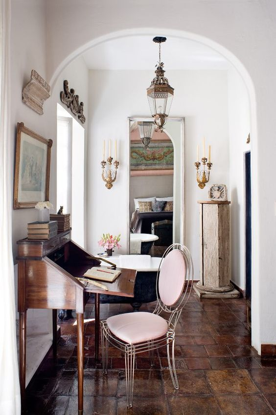 a sophisticated home office with a vintage bureau desk, a sheer blush chair, vintage lamps and candleholders on the walls