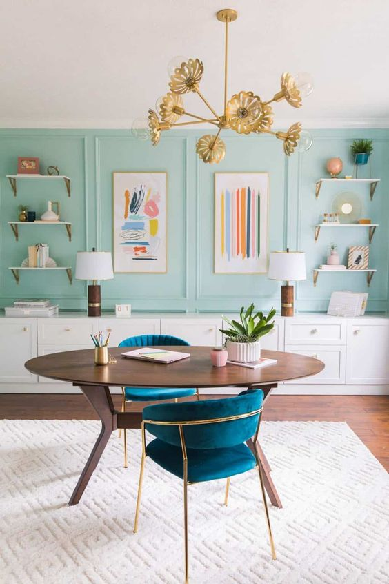 a sophisticated home office with aqua panels, open shelves, a long storage unit, an oval desk and lovely navy chairs