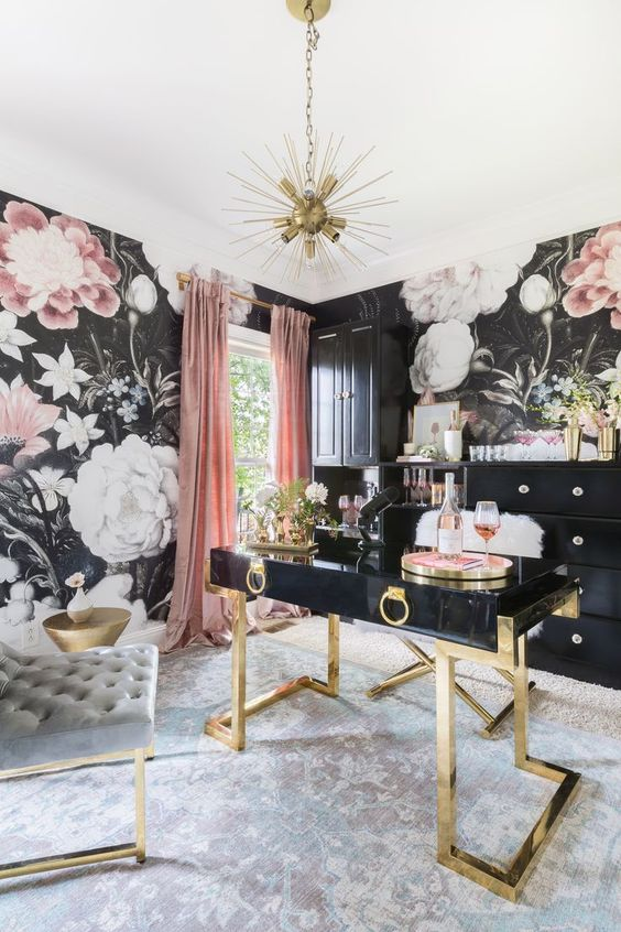 a sophisticated home office with moody floral wallpaper, a black and gold desk, chic tufted chairs, black storage units and a sunburst chandelier