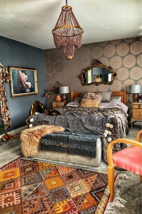 a sophisticated maximalist bedroom with an accent printed wall, wooden furniture, dark printed textiles, a vintage mirror and a crystal chandelier