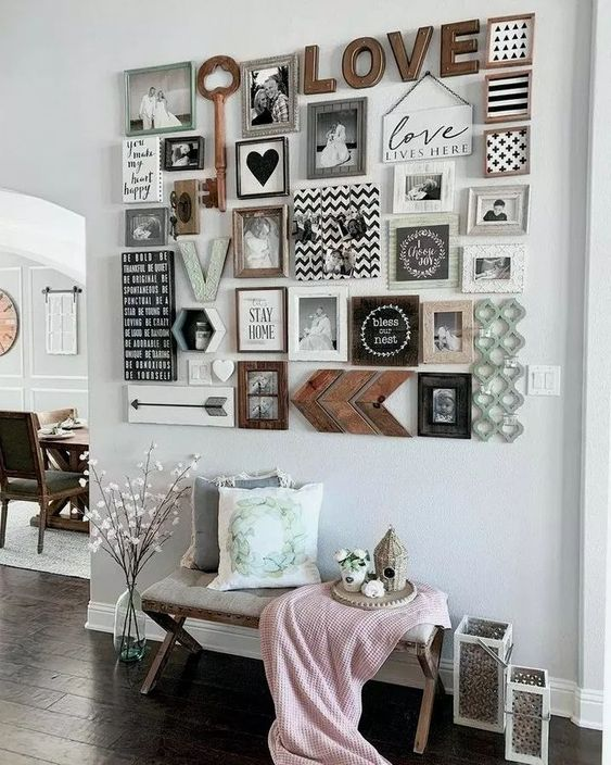 a stylish gallery wall with black and white family pics, wooden keys and signs, hearts and monograms is a lovely idea