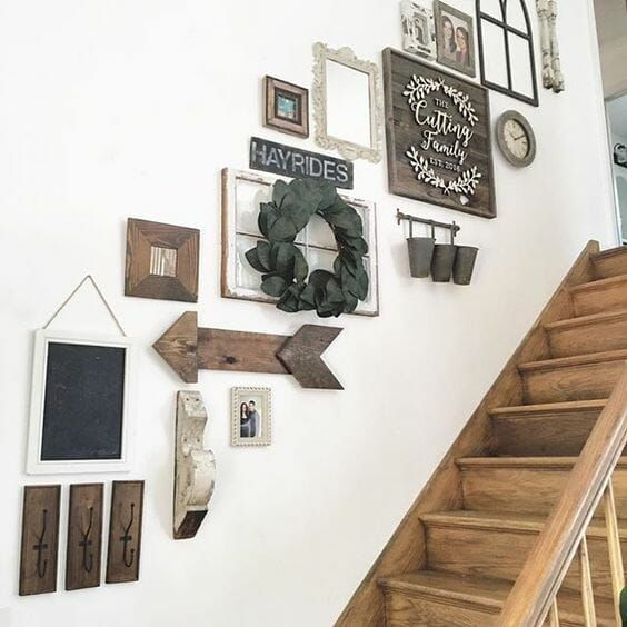 a stylish gallery wall with wooden arrows and signs and artworks in stained frames, mirrors and vintage window frames
