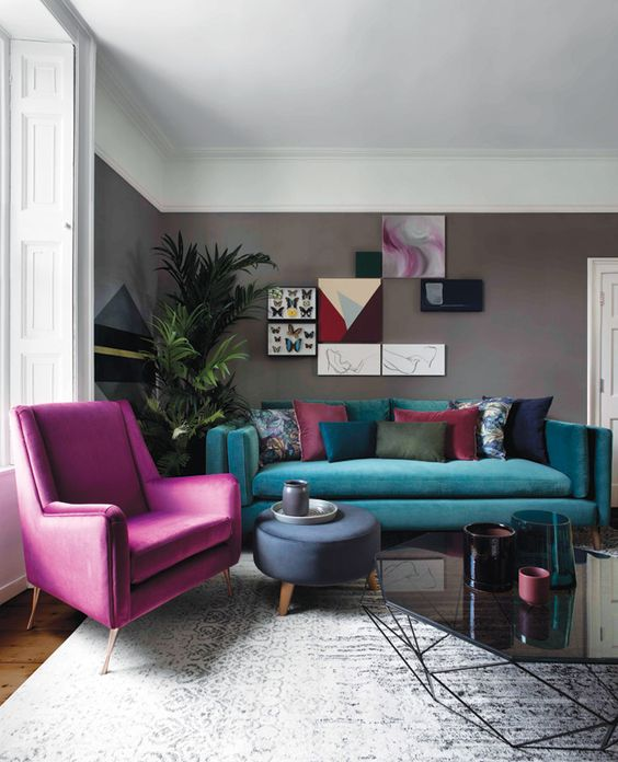 a stylish living room with grey walls, a turquoise sofa and a hot pink chair, a colorful gallery wall and a statement plant