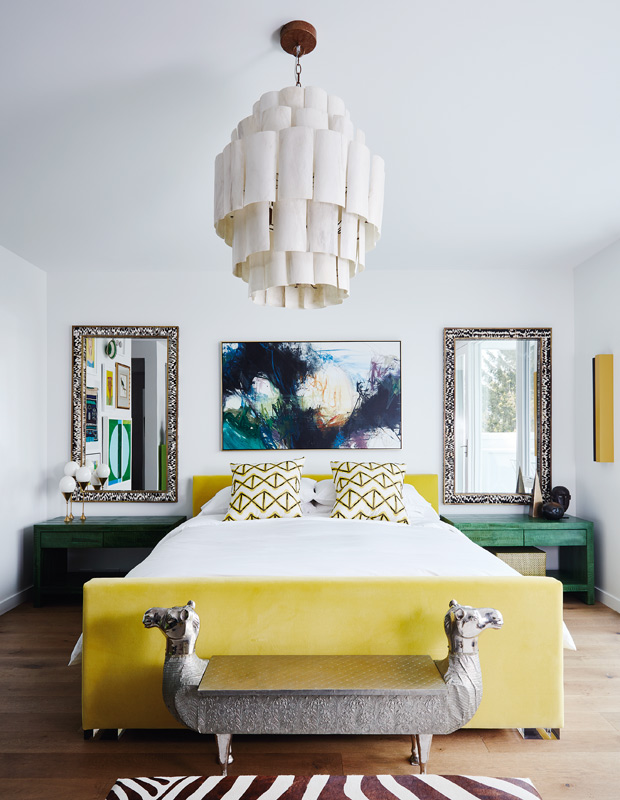 a stylish maximalist bedroom done in white, with a yellow upholstered bed, green nightstands, mirrors, a statement artwork and a catchy chandelier