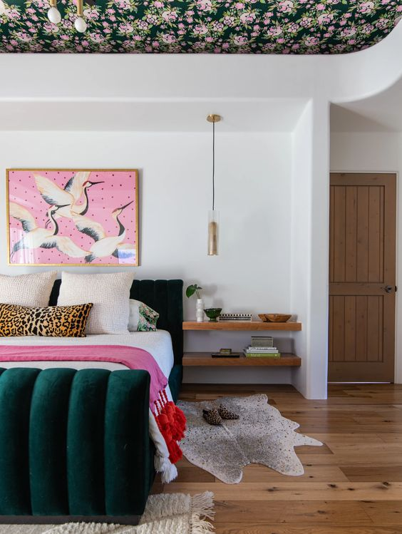 a stylish maximalist bedroom with a floral ceiling, a dark green velvet bed, a bold artwork and pretty rugs plus pendant lamps