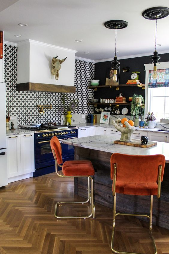 a stylish maximalist kitchen with black walls and an accent tile one, white cabinetry and a navy cooker, rust chairs and a marble countertop
