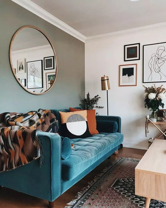a stylish mid-century modern living room with a grey accent wall, a turquoise sofa, printed textiles and a monochromatic gallery wall
