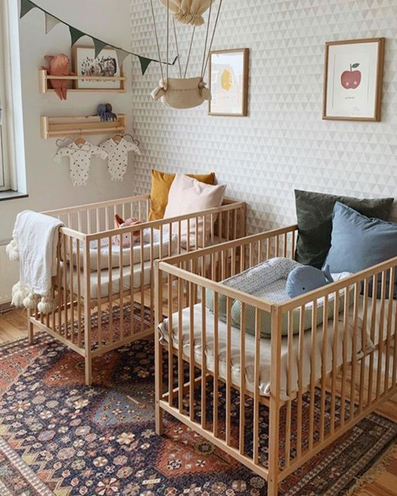 a stylish mid-century modern twin nursery with a wallpaper wall, stained cribs, a printed rug and pastel and printed bedding plus art