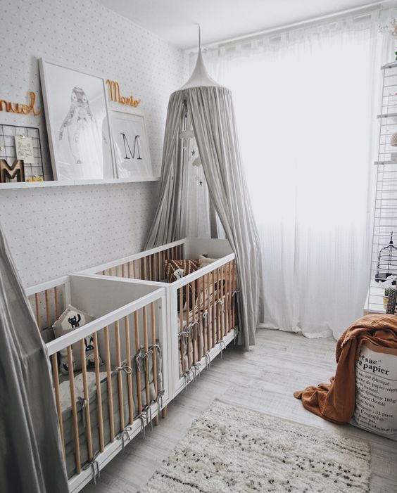 a stylish neutral nursery with white cribs, a rug, grey canopies, a ledge with artworks and lovely textiles