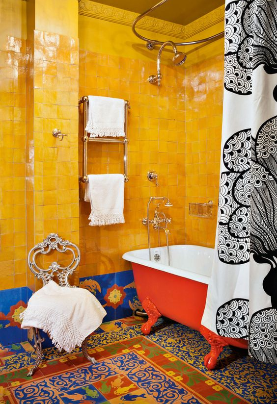 a super bold maximalist bathroom with bold yellow and blue tiles, colorful mosaic tiles on the floor, a red bathtub, a vintage chair