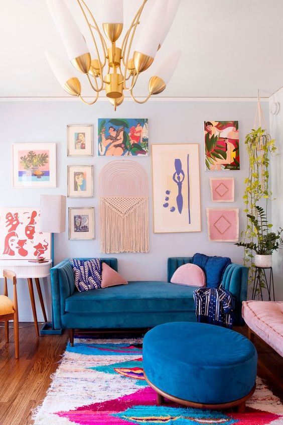 a super colorful maximalist living room with a blue accent wall, a bold blue sofa and ottoman, a colorful gallery wall and potted plants