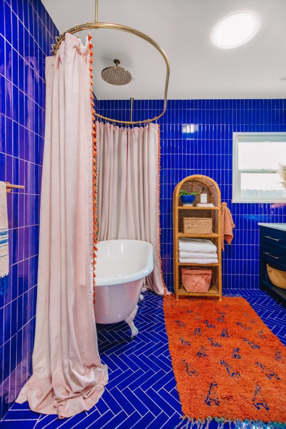 a super vibrant maximalist bathroom clad with electric blue tiles, a vintage tub with a large curtain, an orange rug, a rattan shelf and a black vanity