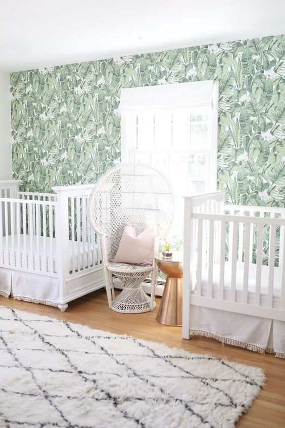 a tropical twin nursery with a banana leaf wall, white cribs and a peacock chair, a printed rug and a metallic side table