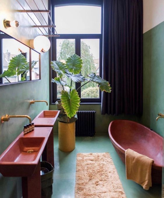 a vibrant bathroom done with aqua-colored wlals and a floor, pink sinks and a bathtub, gold fixtures and a black curtain