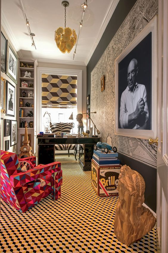 a vibrant maximalist home office with a map and a bold artwork on the wall, a gallery wall, a geometric floor and a printed curtain