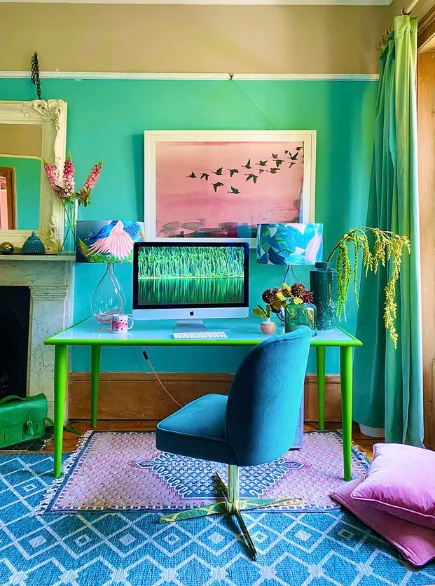 a vibrant maximalist home office with bold ombre walls, a blue and yellow desk, a bold blue chair, colorful almps, rugs and pillows