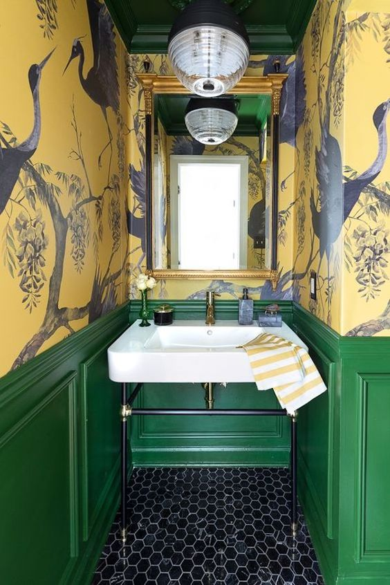 a vintage maximalist bathroom with yellow bird wallpaper walls, green paneling, a black hex tile floor, a mirror in a gilded frame and a lamp