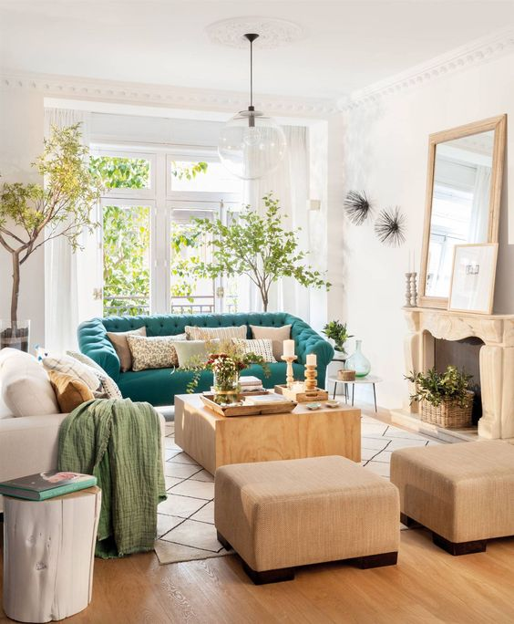 a welcoming living room with a fireplace, neutral furniture, potted trees and a turquoise sofa for a bold color statement