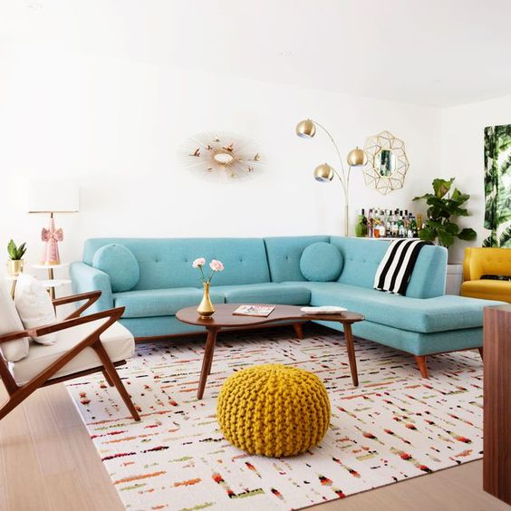 a welcoming mid-century modern living room with a turquoise sofa, elegant mid-century modern furniture and touches of gold for chic