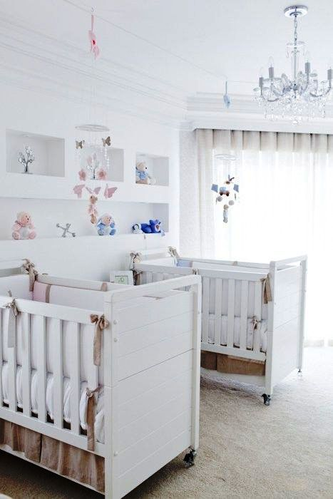 a white twin nursery with pretty cribs, built-in shelves, a crystal chandelier and some pastel and bright toys is cool