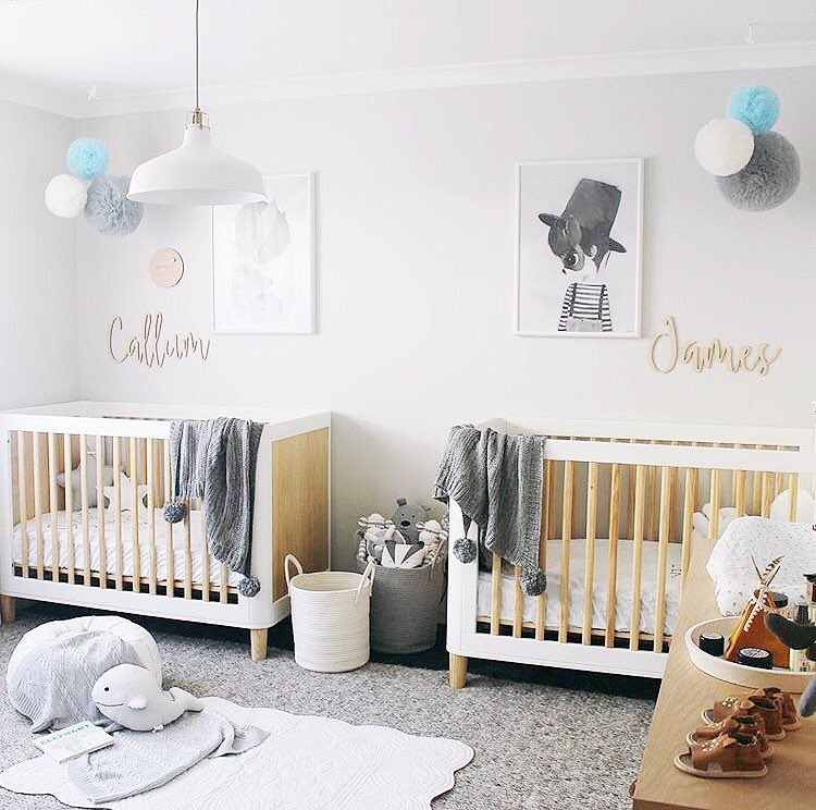 an airy contemporary nursery with two matching cribs, neutral textiles and layered rugs, lovely artworks and pendant pompoms