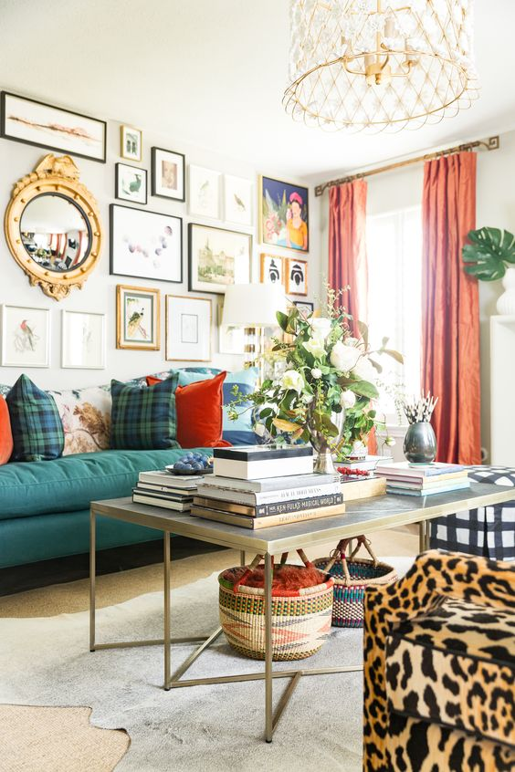 an airy maximalist living room with neutral walls, a green sofa, a large coffee table, a leopard print chair, coral curtains and a lovely chandelier
