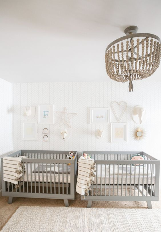 an airy twin nursery with an accent wall, grey crib, a wooden bead chandelier, neutral and printed bedding and a gallery wall