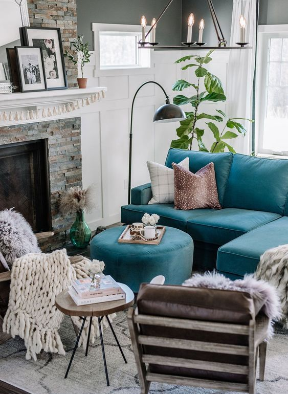 an eclectic living room with a fireplace clad with faux stone, a turquoise sofa and an ottoman, a stool, leather chairs, a chandelier