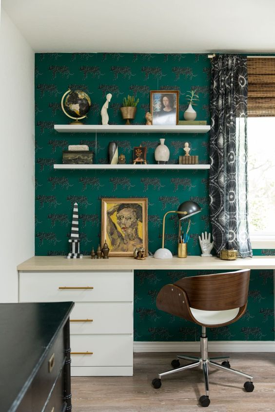 an elegant maximalist home office with a green wallpaper wall, a large desk, a comfy chair, a black dresser, lots of accessories and printed curtains