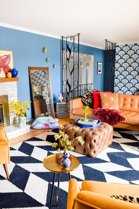 bright maximalist living room with blue walls, a chevron rug, an amber sofa and an ottoman, yellow chairs, a gold table and a fireplace