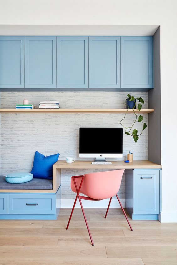 a bright blue home office done with kitchen cabinetry, a small desk and a daybed, a floating shelf is a very welcoming and fresh idea