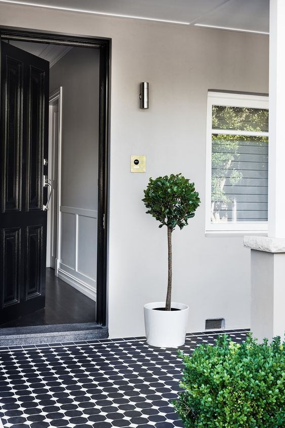 a very laconic and simple modern porch with a black door, black and white patterned tiles, some potted greenery is a chic idea to repeat