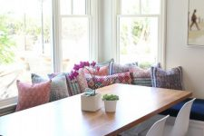 03 a bright boho dining space with a corner window, shades, a corner banquette seating, a dining table and white chairs