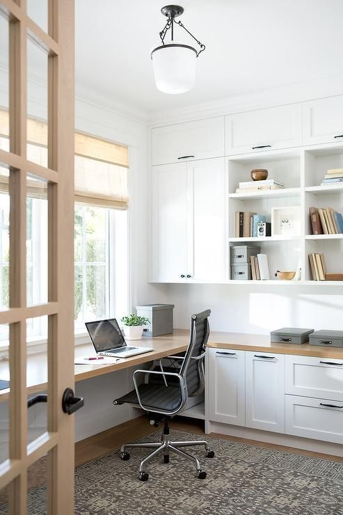 a modern farmhouse home office with white shaker kitchen cabinets, a floating desk and shades plus a printed rug