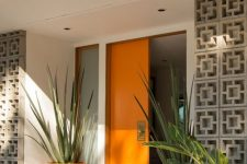 03 a very chic mid-century modern front porch with a bold orange door and planters with oversized plants plus screens to protect from the sun
