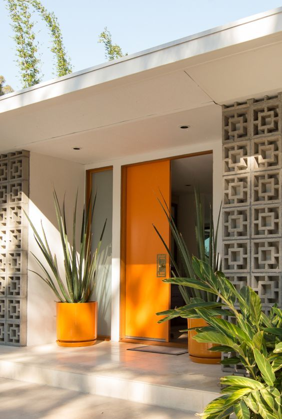 a very chic mid-century modern front porch with a bold orange door and planters with oversized plants plus screens to protect from the sun