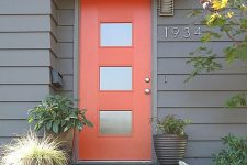 04 a bold modern mini porch with a red glass insert door, mismatching planters with various greenery and house numbers on the wall
