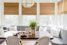 04 a chic and lovely dining space with corner windows, a large upholstered banquette seating, a dining table and rattan chairs